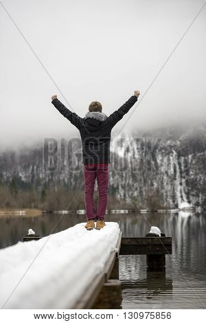 View from behind of a man raising his arms in triumph high in the air standing at the end of an old wooden pier covered with snow on a peaceful lake.