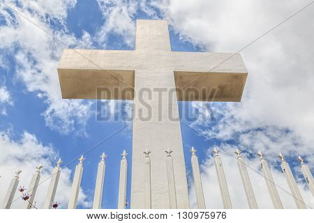 Front view of the Mt. Helix cross with fence railing and a background of a cloudy blue sky in La Mesa, a city in San Diego, California.