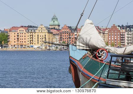 Old City Buildings And Old Boats On Water Under Blue Sky In Stockholm, Sweden.