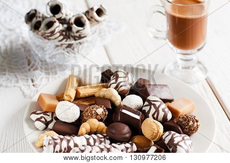 Delicious chocolate dessert on a white wooden table with cup of coffee cappuccino . Vase with cookies close-up on lace white napkin. Front view of chocolate candies, focus on foreground.