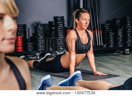Portrait of blonde woman stretching her back in fitness class before training on sports center