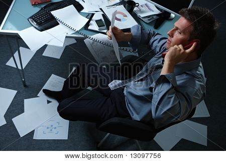 Tired businessman calling from office with shoes off papers lying all around, picture taken from high angle.