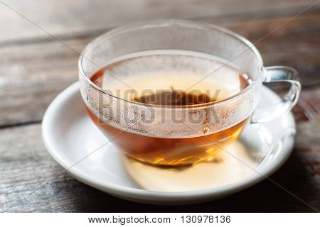 Cup of hot black tea close-up. Glass cup on saucer front view. Cup with tea leaves on dark wooden background.