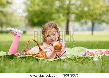 Little girl holding an apple in his hand on a picnic
