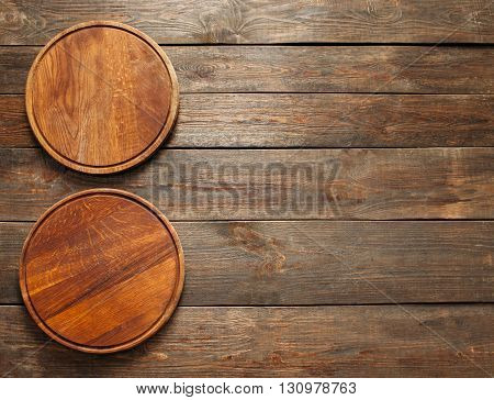 Two empty wooden pizza plates on the wooden table. Vertical line. Flat lay of empty wooden pizza plates. Free space. Sidepiece