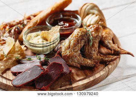 Meat beer snacks on white plate. Grilled chicken wings, pastirma, cheese and sauces top view. Close-up of beer snacks with focus on foreground