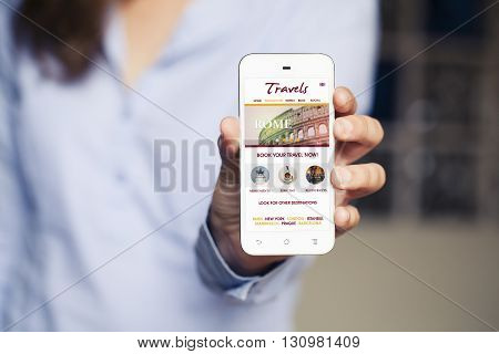 Travel booking website in a smart phone screen. Woman holding mobile phone in the hand.