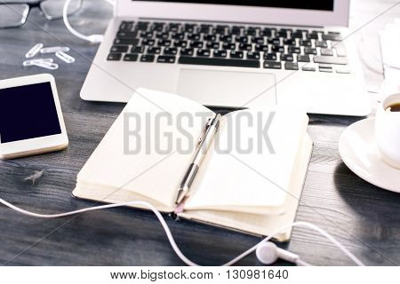 Closeup of blank copybook with pen on dark wooden desk with laptop keyboard smartphone and other items