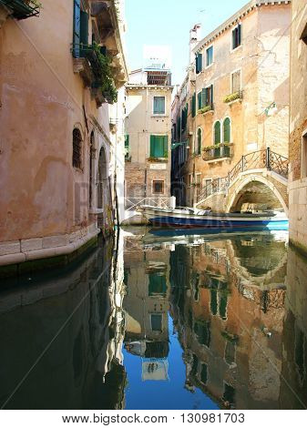 Colorful narrow lateral canal church Santa Maria dei Miracoli and pedestrian bridge in the sestiere of Cannaregio at morning in Venice Italia