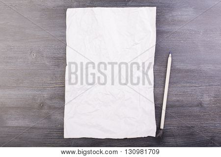 Crumpled paper and pencil on dark wooden desktop. Mock up