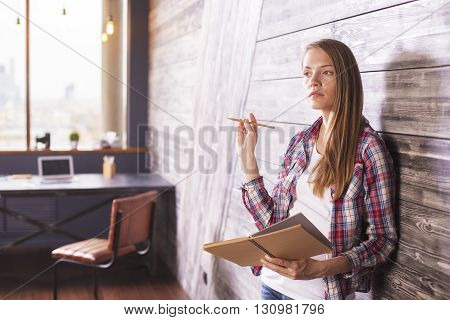 Thoughtful woman in interior with notepad and pencil in hands