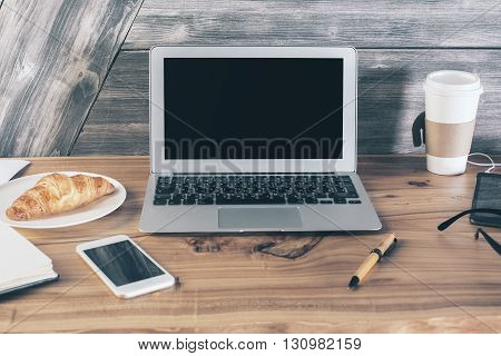 Closeup of wooden designer desktop with blank laptop coffee croissant and other items. Mock up