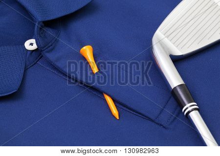 Detail of blue polo shirt and golf equipments