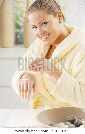 Happy young woman wearing bathrobe, using hand cream, smiling.