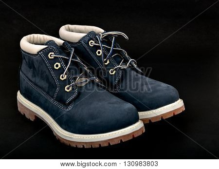 Pair of navy blue lady's boots with shoelace and sole up on black background.
