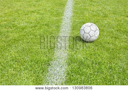 Used Soccer Ball On Grass By A Sideline.