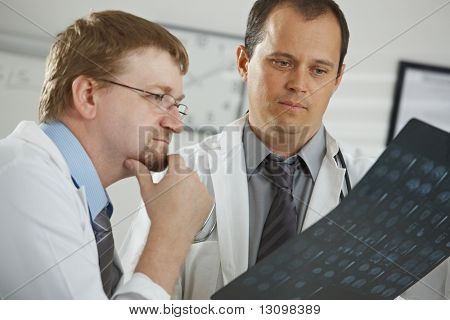 Medical office - middle-aged male doctors having consultation over computer tomograph scan.