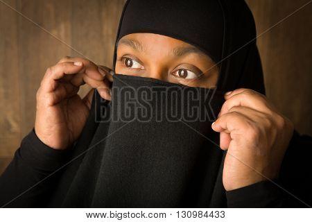 African islam woman hiding behind a black veil