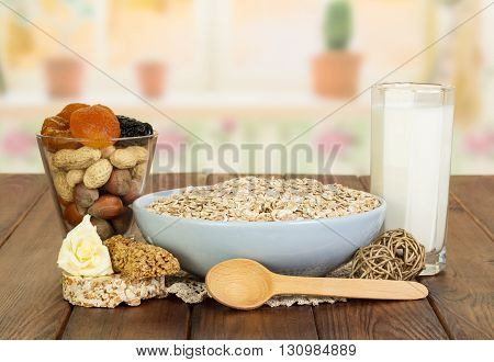 Healthy Eating: a bowl of oatmeal, a glass of milk, dry fruits and nuts on the background of the kitchen.