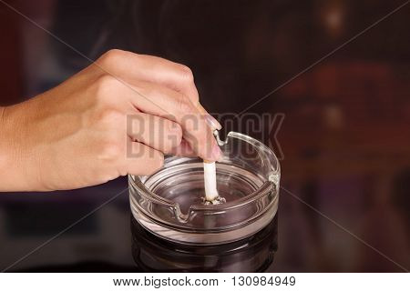 The female hand puts a cigarette in an ashtray on an abstract brown background.