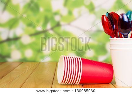 Bright disposable cups and plastic spoons on an abstract green background.