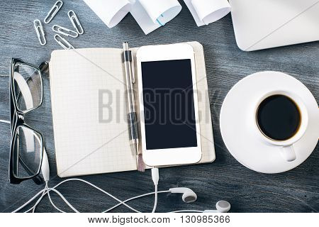 Blank smartphone with headphones on top of notepad placed on dark wooden table with ceramic coffee cup glasses and other items. Mock up