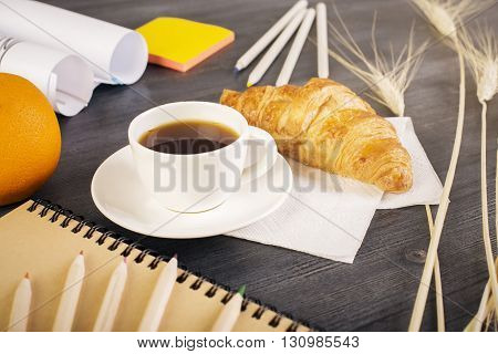 Closeup of wooden desktop with orange croissant coffee cup stationery wheat spikes and paper rolls