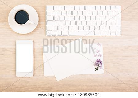 Top view of wooden desktop with blank smart white phone emty card coffe cup and keyboard. Mock up