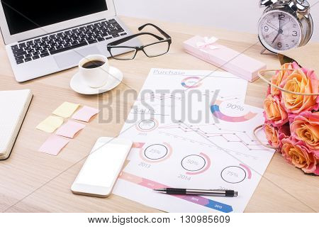 Creative designer desktop with business report blank white smart phone screen flowers laptop coffee cup alarm clock and other items. Mock up