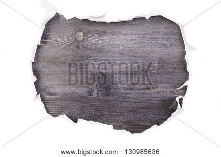 Torn paper revealing dark wooden surface. Mock up