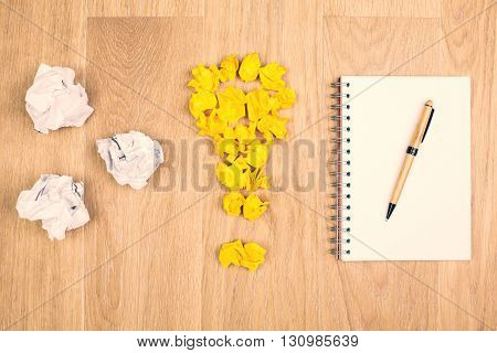 Idea concept with crumpled paper lightbulb and white spiral notepad with pen on wooden desktop