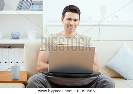 Casual man wearing beige t-shirt using laptop computer at home, sitting on couch, looking at camera, simling.