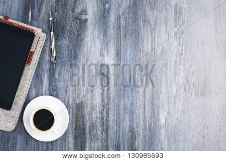 Top view of wooden desktop with coffee cup tablet and pen. Mock up