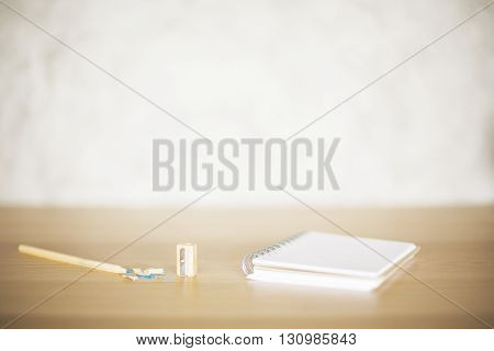 Wooden desktop with spiral notepad pencil sharpener and filings on blurry concrete background