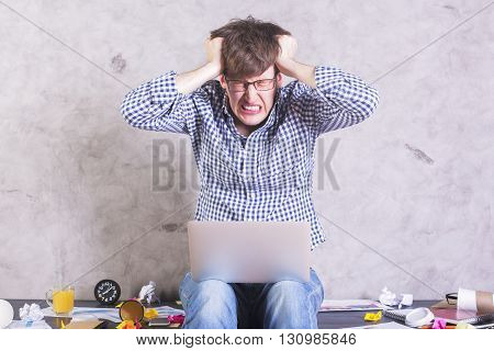 Crazy frustrated businessman with laptop sitting on messy office desktop and pulling his own hair