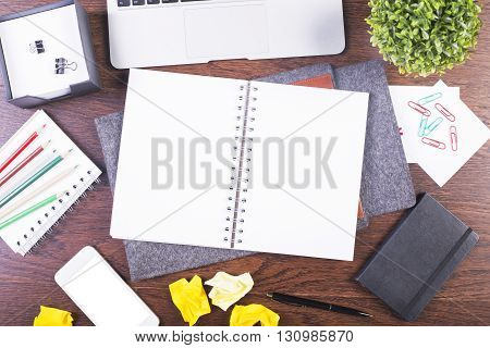 Top view of creative dark wooden desktop with blank spiral copybook white smartphone and various office tools. Mock up