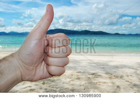 Closeup Thumbs Up On The Beach Background Blue Sky