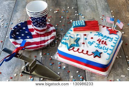 4th of July celebration cake with plates and cups on wooden surface