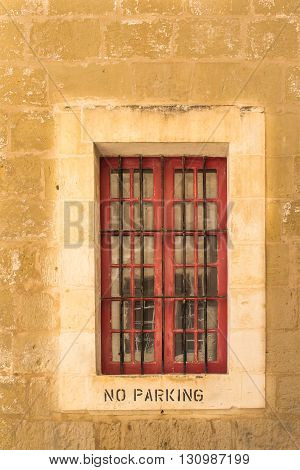 Window of a stone house with a lighter frame and a grid. No parking instruction on the frame. Former capital Mdina at the mediterranean island Malta.