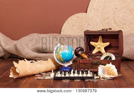 All travel: the globe, chess, old map and compass on brown background.