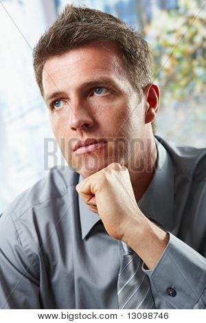 Portrait of confident businessman focusing looking up leaning chin on fist in closeup.