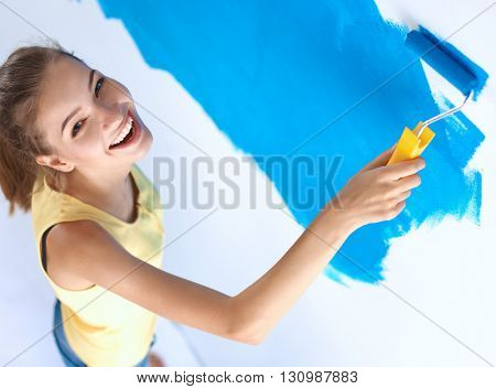 Beautiful young woman doing wall painting