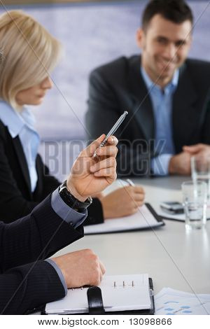 Closeup of hands on business meeting at office, businessman pointing with pen.