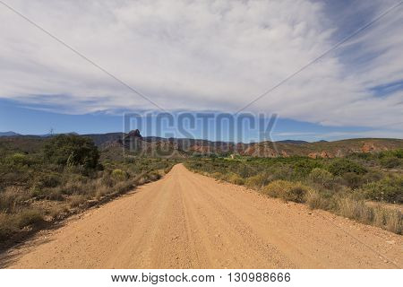 Dirt road leading over a high mountain pass in daytime