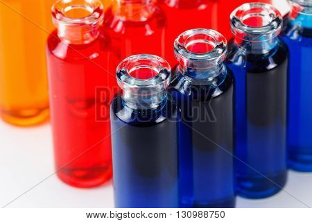 Blue, red and orange liquid in chemical lab test tubes. Closeup background on white