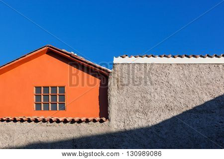 orange house, window and wall on the sky background