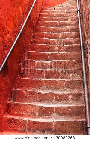 beautiful ancient staircase and red wall