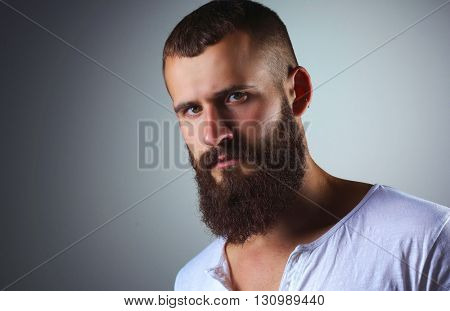Portrait of handsome bearded man standing, isolated on grey bac