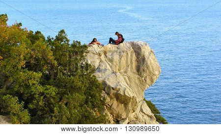 Group of young people resting on the ledge of the cliff above the sea