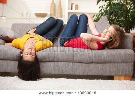 Happy teenage girls lying on sofa, listening to music and having fun at home.